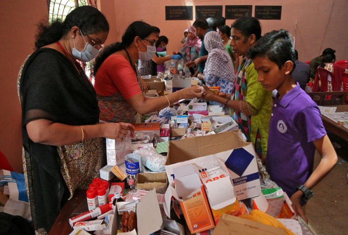 Flood-affected people receive free medicines inside a college, which has been converted into a temporary relief camp, in Aluva. Reuters photo