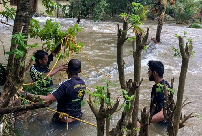 Navy personnel along with volunteers rescue people who were trapped in the flood-hit areas in Thrissur district on Monday, Aug. 20, 2018. (Coast Guard Photo via PTI)