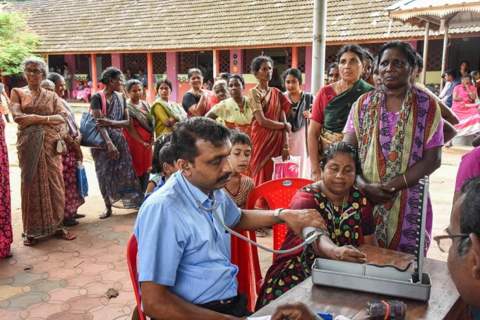 Flood affected people queue up for health check-up at a relief camp at North Paravoor in Kochi. PTI photo