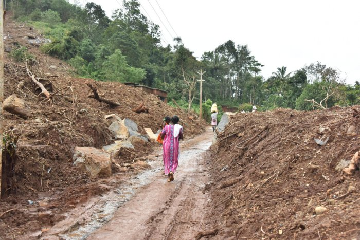 A woman walks through a rubble of houses which were destroyed by landslide at Aanoth Ammara in Wayanad district on Thursday. DH photo by Janardhan BK