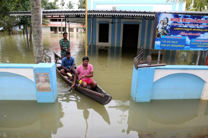Men paddle their boat through the lawns of a partially submerged church at Kuttanad in Alleppey district. (Reuters file photo)