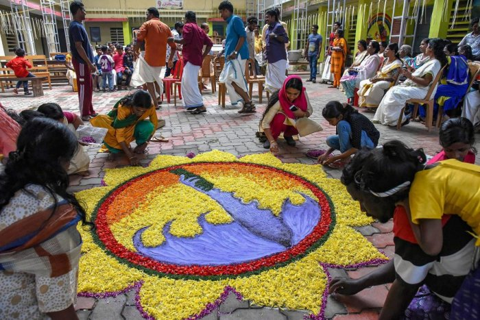 Women make a rangoli as they celebrate Onam at a flood relief camp in Kochi. PTI file photo