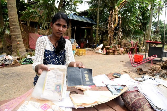 A woman shows her documents damaged due to Kerala floods at Annamanada in Thrissur on Sunday. PTI
