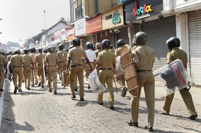 Police personnel patrol at a closed market during Congress party's statewide 'black day' strike on the issue of the entry of two women of menstruating age into the Sabarimala temple of Lord Ayyappa, in Kozhikode. PTI file Photo
