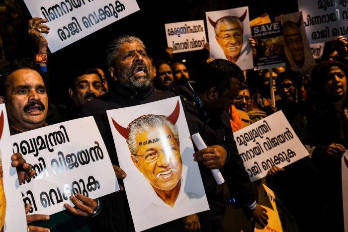 Protestors hold placards bearing the image of Kerala Chief Minister of Kerala Pinarayi Vijayan during a demonstration over two women entering the Sabarimala Ayyapa temple. AFP