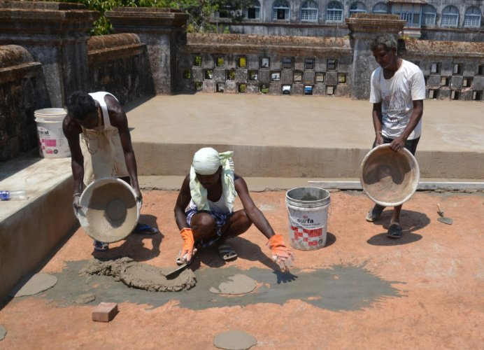 Workers cover the damaged part of Madikeri Old Fort with concrete mixture.