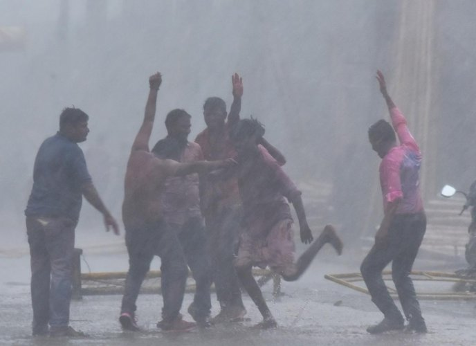 Holi revellers dance in the heavy rain in Hubballi on Monday. (Right) The rain affected the movement of vehicles on Lamington Road in the city. DH Photos/ Tajuddin Azad