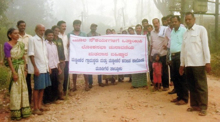 Villagers of Maddikere hold a banner declaring their intent to boycott the Lok Sabha elections.