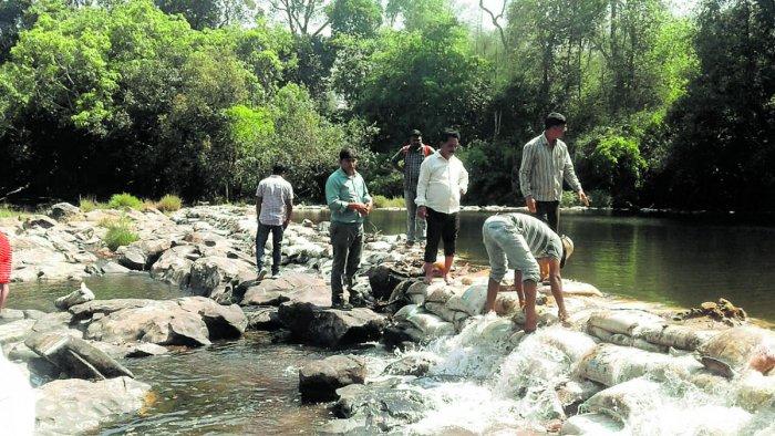 Officials clear illegal bunds constructed across River Cauvery near Kushalnagar.