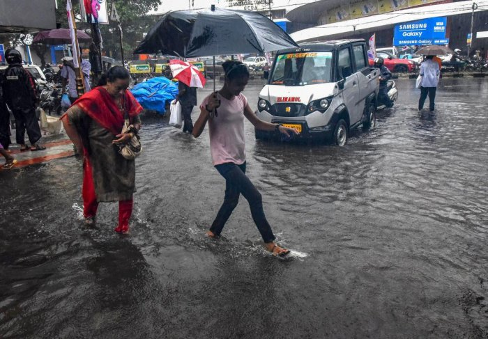 Pedestrians hold umbrellas while trying to make their way across a street in pouring rain in Kochi. PTI file photo.