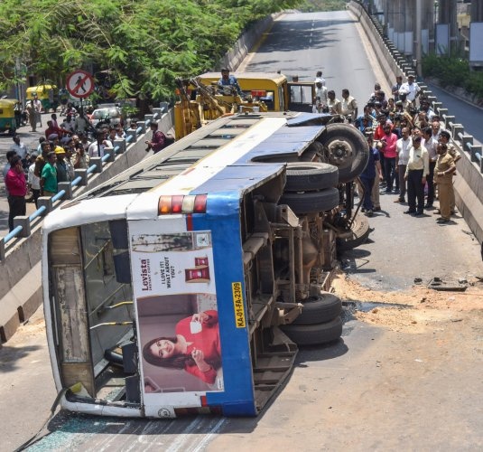 BMTC bus which turned turtle after hitting a divider on west of Chord road in Rajajinagar in Bengaluru on Wednesday. (DH Photo/SK Dinesh)