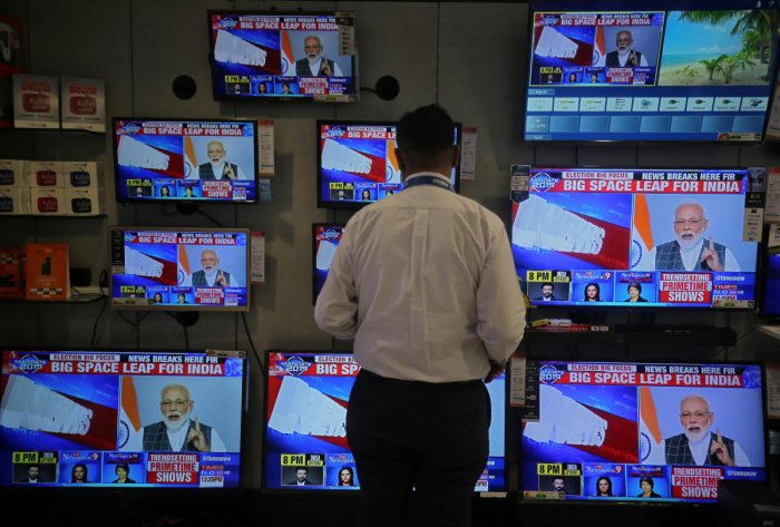 A salesman watches Prime Minister Narendra Modi addressing to the nation, on TV screens inside a showroom in Mumbai, India, March 27, 2019. (REUTERS)