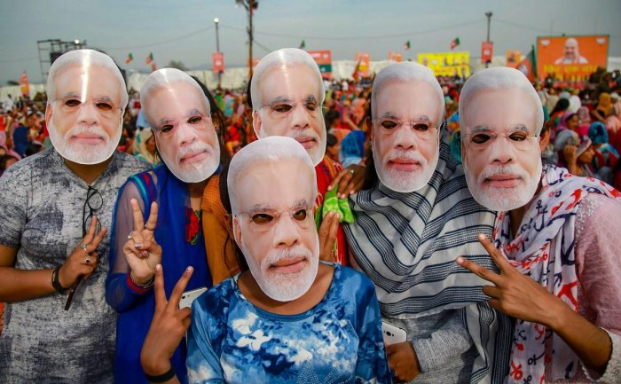 Jammu: BJP supporters wear masks of Prime Minister Narendra Modi to extend their support during a public rally ahead of Lok Sabha elections, at Dumi village near Jammu, Thursday, March 28, 2019. (PTI Photo) (PTI3_28_2019_000139A)