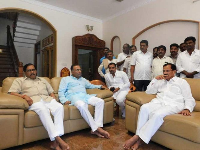 Deputy Chief Minister G Parameshwara, KPCC president Dinesh Gundu Rao holds talks with Tumkur MP S P Muddahanumegowda at latter's residence in Bengaluru on Friday. DH PHOTO