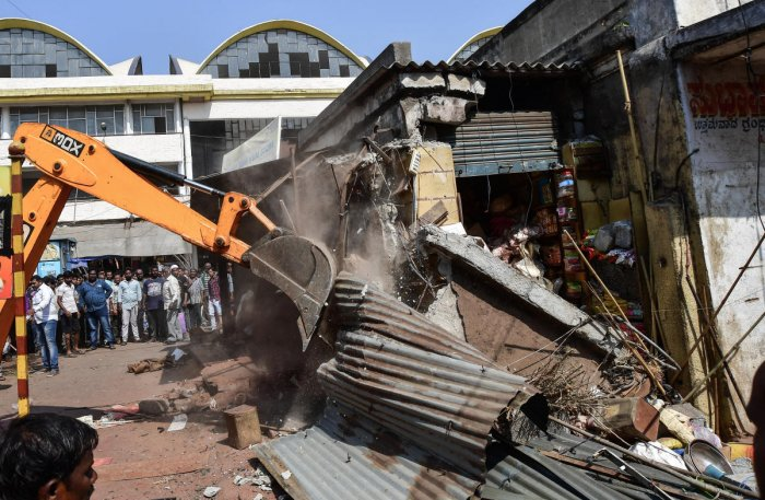 A crane pulls down an unauthorised shop in KR Market on Friday. DH PHOTO/ANAND BAKSHI