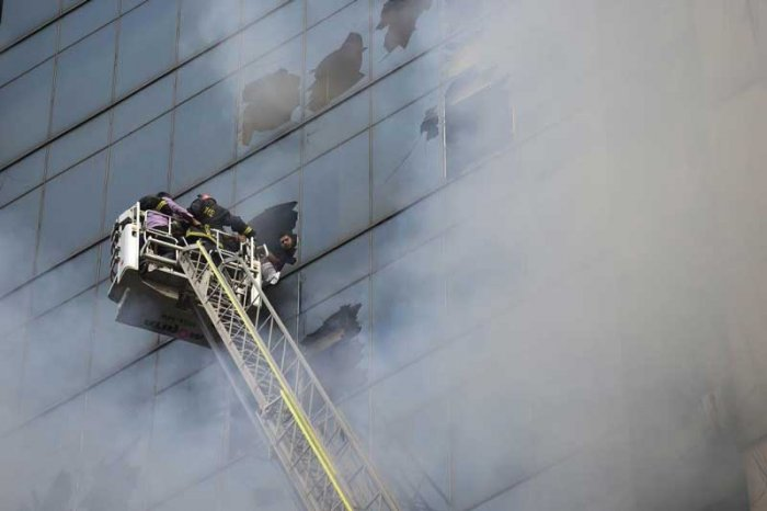 The blaze that burned for several hours on Thursday trapped people inside the building, some shouting for help from windows on upper floors and the roof. (AFP Photo)