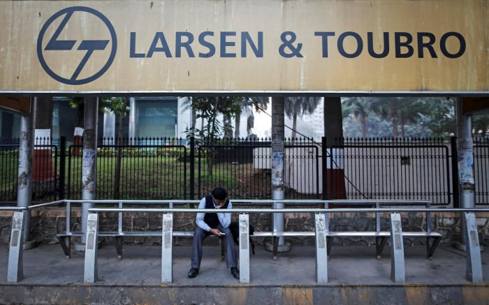 FILE PHOTO: A man waits at a bus-stop with an advertisement of Larsen & Toubro outside the company's manufacturing unit in Mumbai. REUTERS