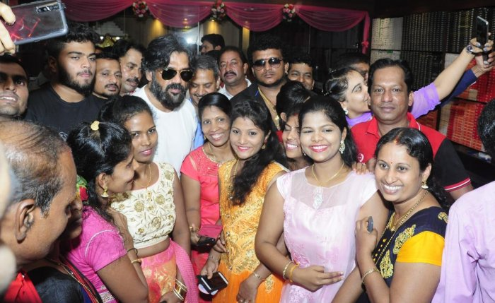 Fans click selfies with actor Suniel Shetty during his visit to Udupi on Friday.