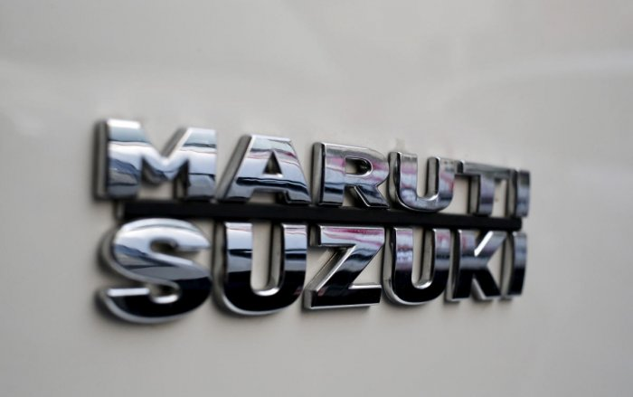 The logo of Maruti Suzuki India Limited is pictured on a car parked outside a showroom in New Delhi. PTI File copy