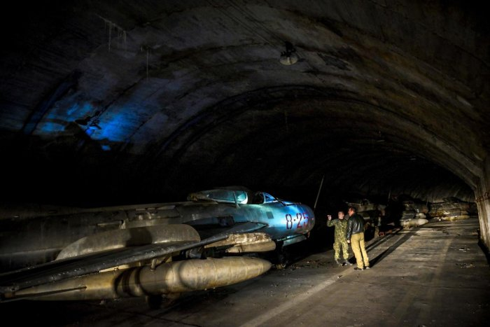 Albanian military personnel walk next to MIG-19 jet fighters inside the main tunnel of the Gjader Air Base built near the city of Lezhe. (AFP Photo)
