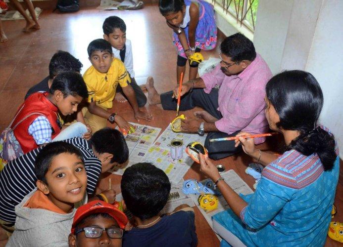 Artist Nageshwar trains students in preparing 'Cheriyal' masks at the Crafts Mela in Madikeri.