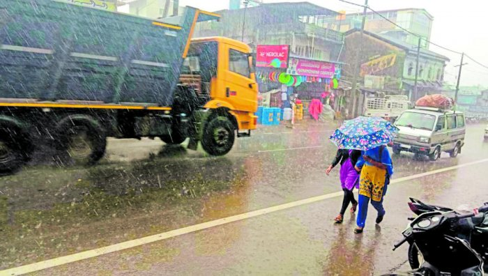 Women take shelter under umbrella from showers in Belur in Hassan district on Monday. DH Photo