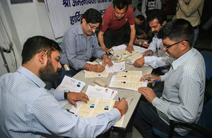 Devotees fill registration forms for the annual Amarnath yatra at Punjab National Bank, in Jammu onTuesday. (PTI Photo)