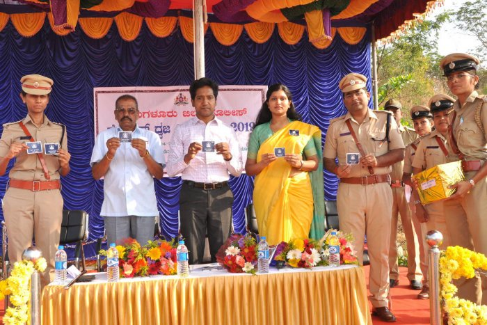 Deputy Commissioner Dr Bagadi Gautham releases police flag stickers during the Police Flag Day programme in Chikkamagaluru on Tuesday.
