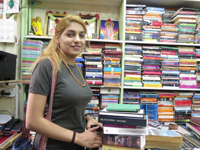 Mina G.H. from Iran, stands next to a stack of books she plans to purchase at a bookstore in Bengaluru on April 2, 2019.