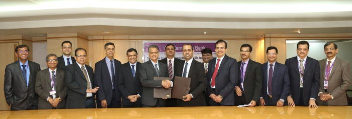 Mahabaleshwara M S, Karnataka Bank MD and CEO, exchanges an MOU with Sam Ghosh, MD, Financial Service, Bharti Enterprises Ltd, in Mangaluru.