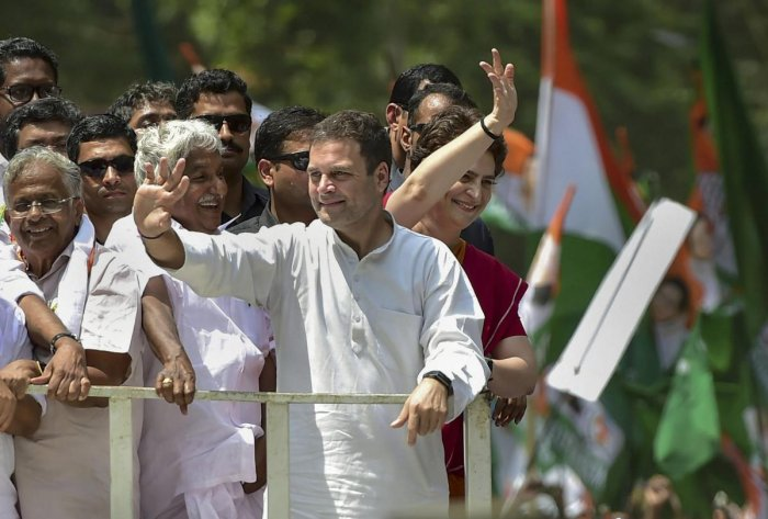 Congress President Rahul Gandhi along with party General Secretary and Uttar Pradesh - East in charge Priyanka Gandhi Vadra and other leaders wave at party supporters during a roadshow ahead of the former's nomination filing, ahead of the Lok Sabha electi