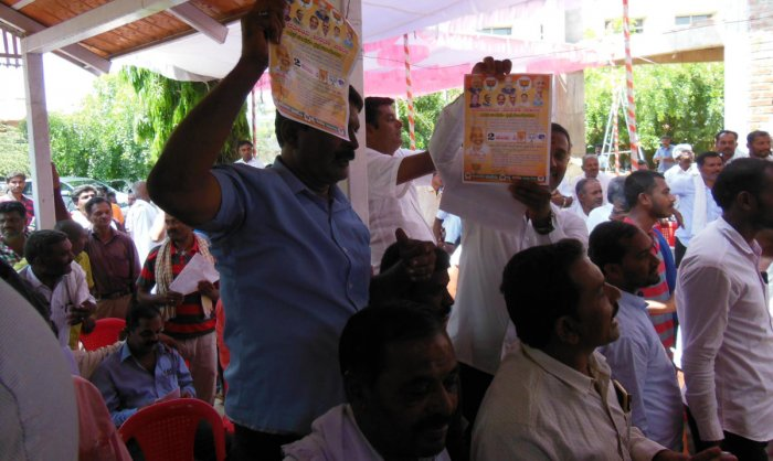A group of people display BJP pamphlets at a Congress meeting at Channarayapatna, Hassan district on Thursday.