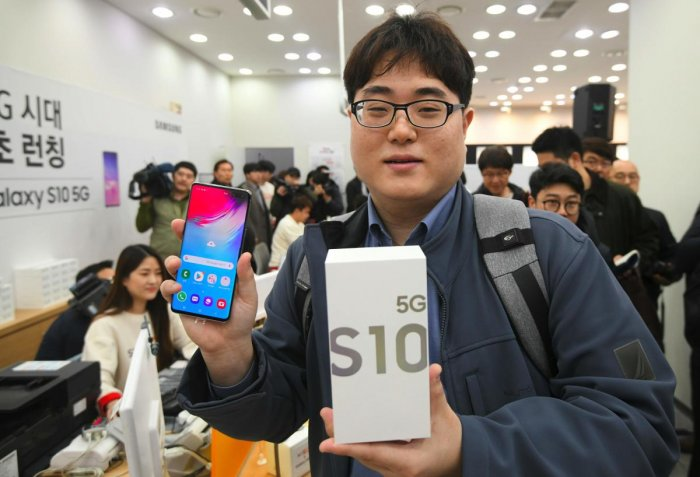 The day's first SK Telecom 5G customer shows his new Samsung Galaxy S10 5G smartphone during a launch event at an SK Telecom shop in Seoul on April 5, 2019. - The world's biggest smartphone and memory chip maker Samsung Electronics warned of a 60 percent-