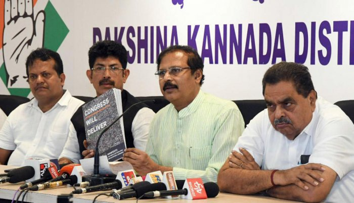 KPCC Vice President V R Sudarshan releases the Congress manifesto 'We will deliver' at the district Congress committee office in Mangaluru on Friday. Former minister B Ramanath Rai and District Congress Committee spokesperson A C Vinayraj look on.