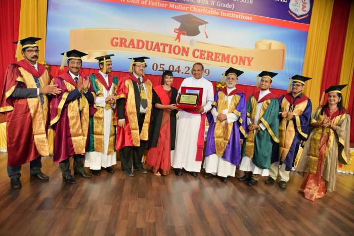Mangaluru Bishop and Father Muller Charitable Institutions (FMCI) President Rev Dr Peter Paul Saldanha presents the Presidents Gold medal to outgoing meritorious student Dr Aleena Thomas at Father Muller Homeopathic Medical College's (FMHMC) 29th graduation ceremony organised at Father Muller Convention Centre in Mangaluru on Friday.