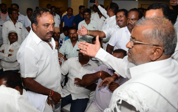 Minister G T Devegowda (right) tries to pacify JD(S) workers at a party meet in Mysuru on Friday. DH photo/Nesara Kadanakuppe
