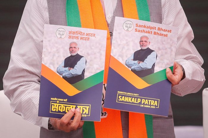 Prime Minister Narendra Modi displays copies of Bharatiya Janata Party (BJP) election manifesto for the April/May general election in New Delhi, India, April 8, 2019. REUTERS
