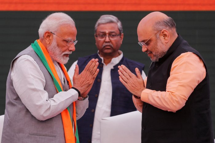 Prime Minister Narendra Modi and chief of India's ruling Bharatiya Janata Party (BJP) Amit Shah, greet each other before releasing their party's election manifesto. (Reuters)