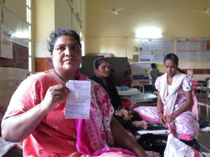 Shanshad, a 36-year-old coolie and a beedi seller, shows her hospital-approved coupon for a blood test, at Victoria Hospital in Bengaluru on April 7, 2019. Although the Arogya Karnataka scheme covered her hernia operation, she found that the government treated all other hospital charges as co-pay - in this case, half of all ancillary charges, including bed and testing charges had to be paid by the patient.