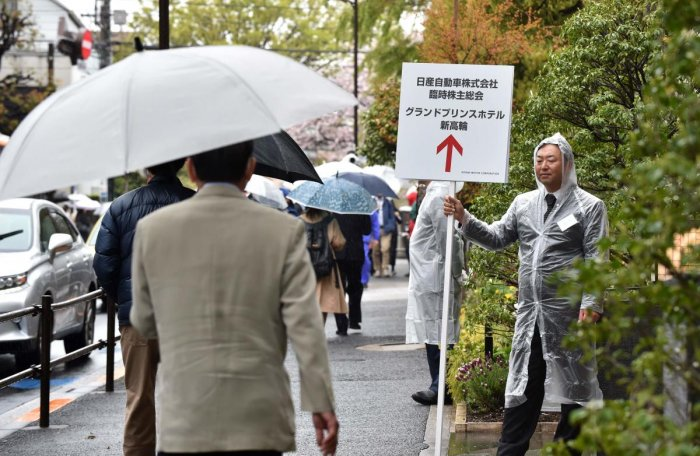 A Nissan Motor employee holds signage on a sidewalk to guide arriving shareholders to a hotel where the company's extraordinary shareholders' meeting will take place in Tokyo on April 8, 2019. AFP