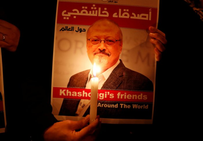 A demonstrator holds a poster with a picture of Saudi journalist Jamal Khashoggi outside the Saudi Arabia consulate in Istanbul, Turkey October 25, 2018. REUTERS