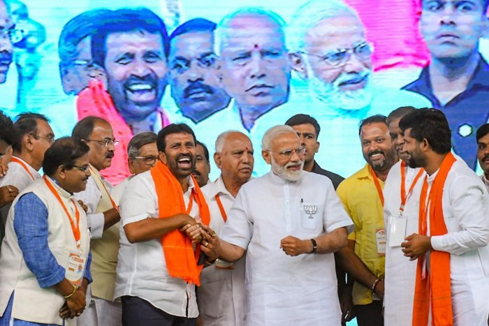 Prime Minister Narendra Modi banters with Chamaraja MLA L Nagendra and Mysuru-Kodagu MP Prathap Simha during the BJP's campaign rally in Mysuru on Tuesday. State BJP president B S Yeddyurappa and others look on. pti