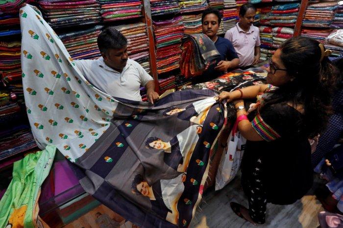 A salesman shows a sari with printed images of Priyanka Gandhi Vadra to a customer inside a shop in Kolkata. PTI file photo