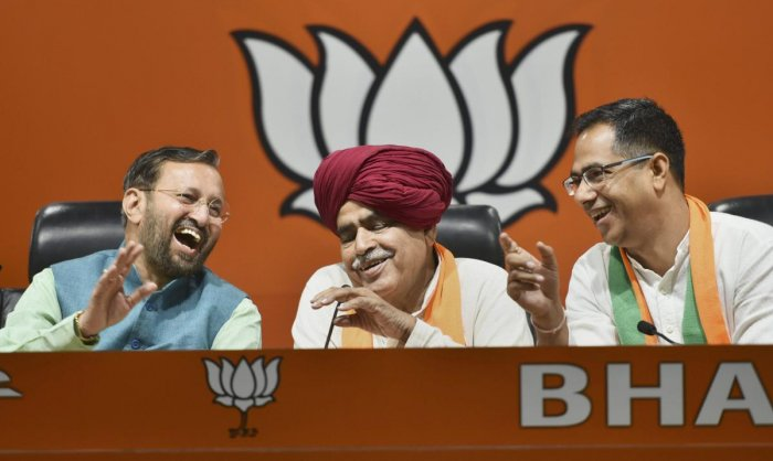 Union Minister and BJP leader Prakash Javadekar share a light moment with Gurjar leader Kirori Singh Bainsla and his son Vijay Bainsla during a press conference after they joined BJP, ahead of Lok Sabha polls in New Delhi on Wednesday. PTI photo