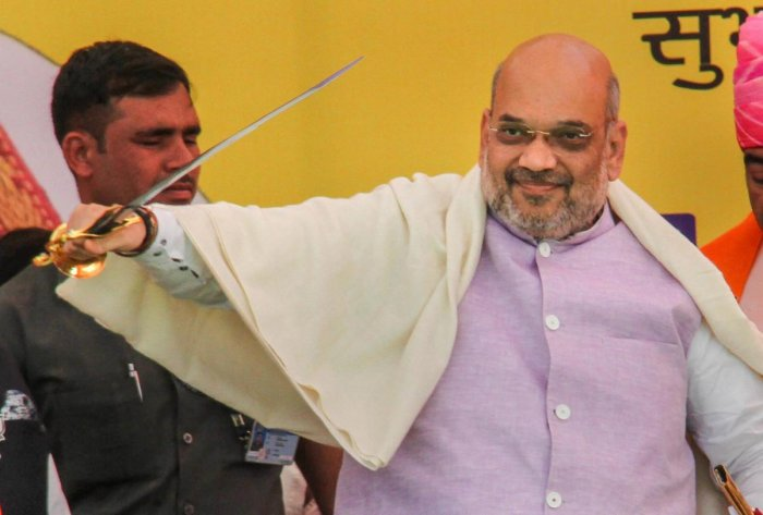 Bharatiya Janata Party National President Amit Shah holds a sword presented to him during an election rally, ahead of the Lok Sabha polls, in Udhampur about 68kms from Jammu, Wednesday, April 3, 2019. (PTI Photo)