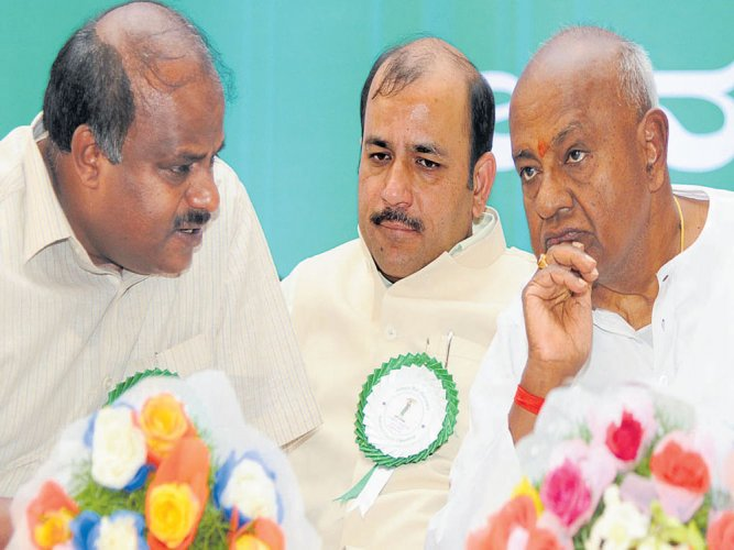 In picture: JDS supremo and former PM H D Deve Gowda (R) in conversation with his son H D Kumaraswamy (L). DH Photo.