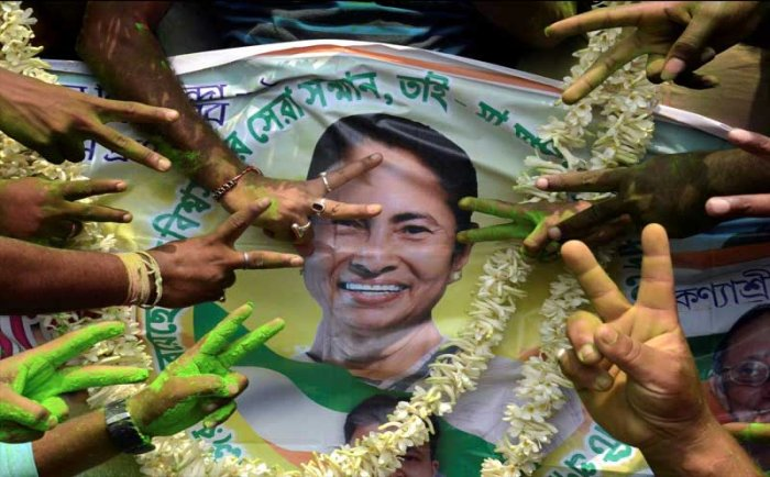 All India Trinamool Congress supporters celebrate with a poster of TMC Chief and West Bengal Chief Minister Mamata Banerjee to celebrate their win in Panchayat elections, in North 24 Parganas, on Thursday. PTI photo.