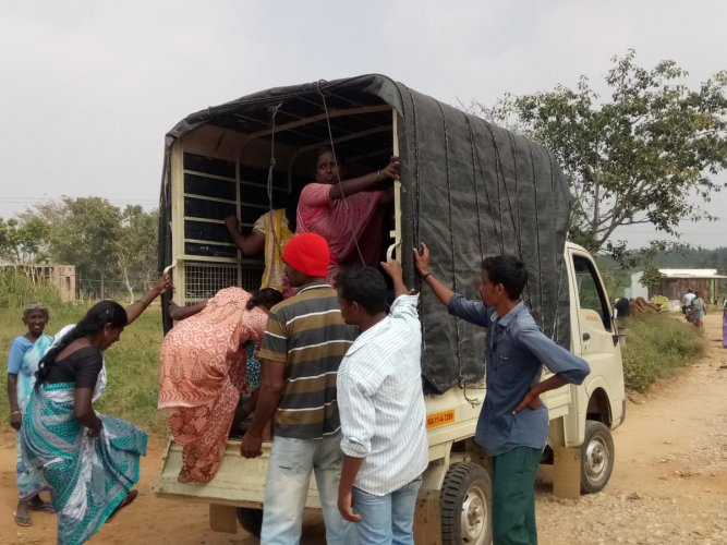 Villagers board a goods autorickshaw at Vadesamudra village, in Pandavapur taluk, Mandya district, on Sunday.