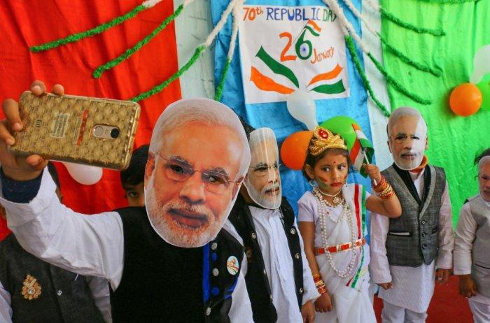 Ajmer: Children wearing Prime Minister Narendra Modi's mask take a selfie during Republic Day celebrations, in Ajmer, Friday, Jan. 25, 2019. (PTI Photo)(PTI1_25_2019_000172B)