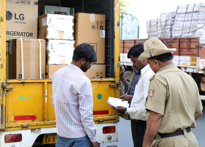 Personnel of a static surveillance team check the vehicle at election checkpost on Magadi Chord Road in Bengaluru on Thursday. DH Photo/Sudheesha K G